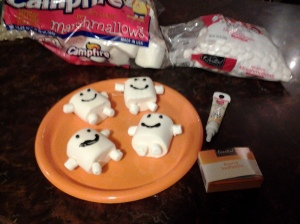 Crisscross toothpicks into large marshmallows. Add four miniature ones for hands and feet. Use black icing to make faces